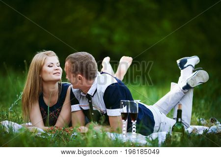 lovers lying on grass in forest. Cute healthy young girlfriend and handsome boyfriend lying on plaid, happy family relationship concept
