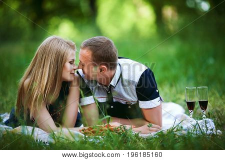 Lovers having fun dating in forest. Beautiful healthy young girlfriend and handsome boyfriend lying on the grass, happy family relationship concept
