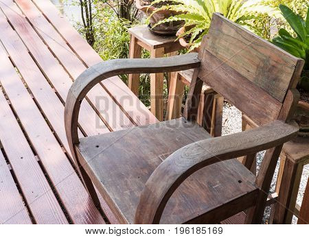 Old wooden armchair on the small terrace with the tree of the country coffee shopnear the small pond.