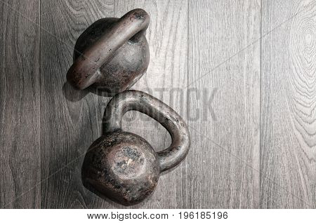Old kettle bell on the gym floor. Sport concept