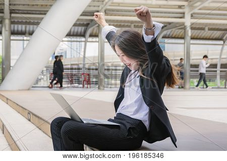 Happy successful business woman with arms up