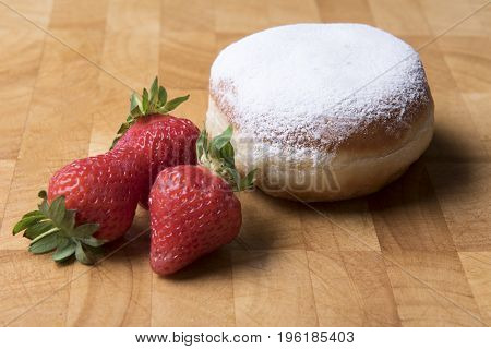 Sugar and jam donuts with strawberries on a wooden background