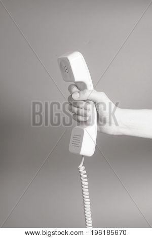 Hand Holding White Telephone Tube On Gray Background.