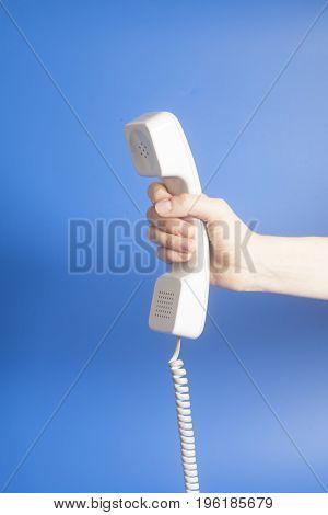 Hand Holding White Telephone Tube On Blue Background