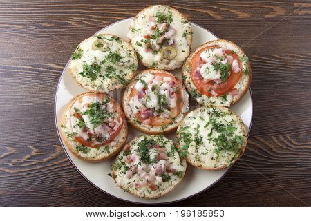 Mini pizza on ready-made buns with tomatoes and sausage