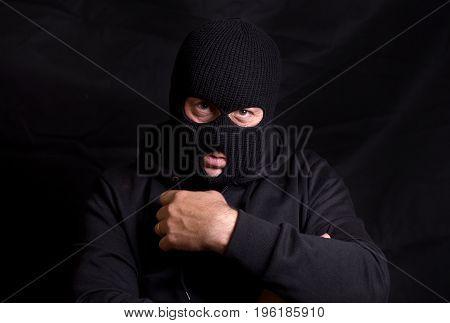 Horizontal image of a threatening man with a balaclava mask