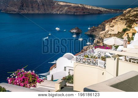 Oia Village, Santorini Cyclade islands, Greece. Beautiful view of the town with white buildings blue church's roofs and many coloured flowers.
