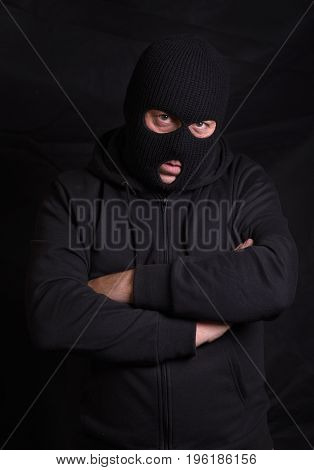 Vertical image of a threatening man with a balaclava mask
