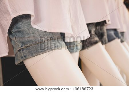 collection of jeans shorts. Modern torn blue jeans shorts on mannequin model.