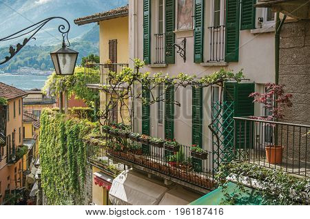 Como, Italy - May 06, 2013. View of Como Lake, balconies with open blinds and bindweed in Bellagio, a charming village between the lake and the mountains of Alps. Lombardy region, northern Italy