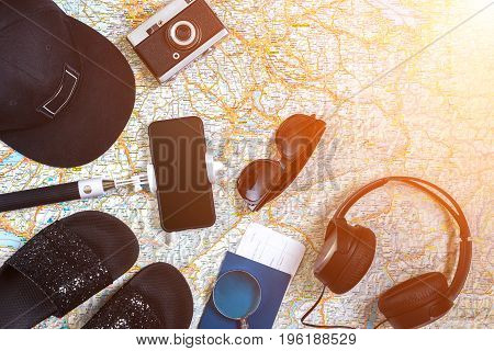 Accessories for travel. Passport, photo camera, smart phone and travel map. Top view. Holidays and tourism concept. Copy space. Still life. Flat lay. Sun flare