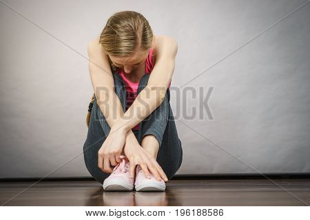 Sad Depressed Young Teenage Girl Sitting By Wall