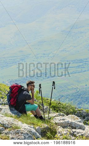 Image of a hiker resting on rocks and looking in the distance in mountains. Location: Apuseni MountainsTransylvaniaRomania.