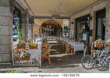 Como, Italy - May 06, 2013. View of restaurant tables and chairs on pedestrian walkway in Bellagio, a charming village between the lake and the mountains of the Alps. Lombardy region, northern Italy