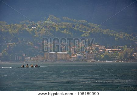 View of Lake Como in a cloudy day with rowers in the foreground in Bellagio, a charming tourist village between the lake and the mountains of the Alps. Located in the Lombardy region, northern Italy