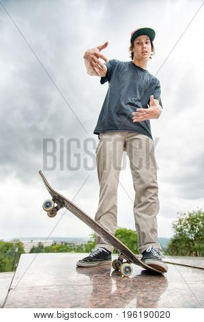 A young long-haired skater in a T-shirt and a full-length cap is standing with a skateboard on the background of the cityscape