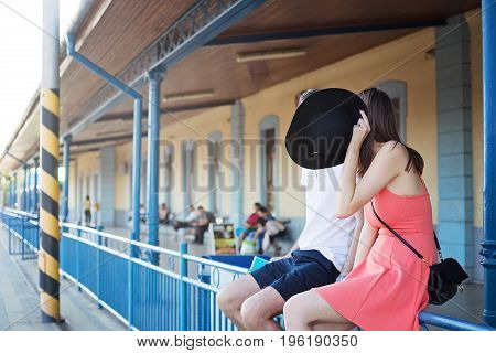 Young caucasian couple sitting on the railings at the trainstation girl holding black hat in front of their faces to hide themselves.