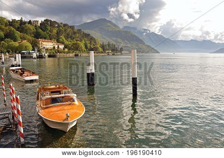 Como, Italy - May 06, 2013. View of Lake Como in a cloudy day with motorboat and harbor in Bellagio, a charming village between the lake and the mountains of Alps. Lombardy region, northern Italy