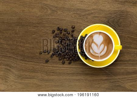 Top view of Latte coffee or cappuccino coffee in yellow cup with latte art decorated by coffee beans on wooden table.