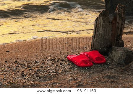 Summer vacation concept. red Flipflops on a sandy ocean beach. Wild uncomfortable beach. The sunset, the beach, the remains of the old pier.