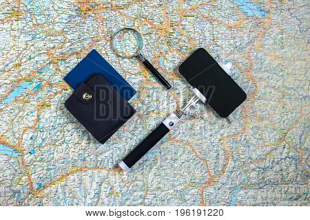 Travel accessories set on the map background: smart, passport and selfish stick. Top view point. Flat lay. Still life. Copy space