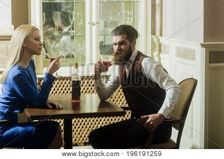 Woman and man drinking from martini glasses. Girl and hipster sharing bottle of wine in restaurant. Couple in love. Alcohol appetizer addictive and convive. Unhealthy lifestyle. Bad habits
