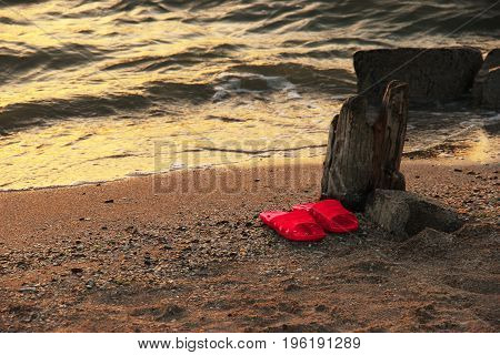 Summer vacation concept. red Flipflops on a sandy ocean beach. The sunset the beach the remains of the old pier.