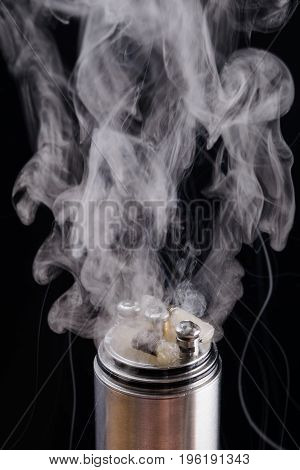 Two spirals with cotton impregnated with liquid emit smoke on a black background