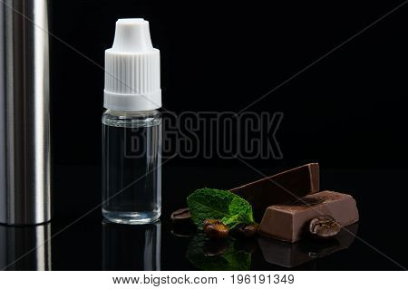 Chocolate flavor with mint aroma in a bottle in the form of liquid on a black background