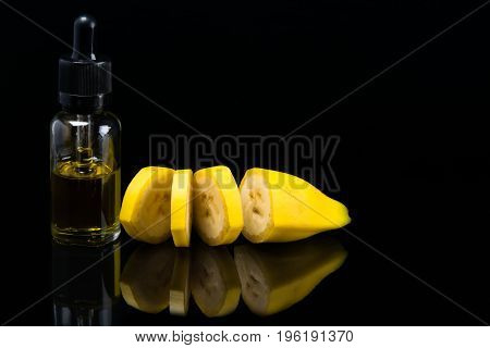 Sliced banana next to a bottle of fragrance on a black background