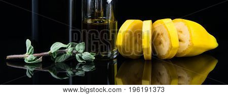 Liquid with banana flavor next to a fragrant green sprout on a black background