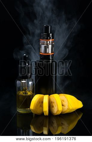 Liquid with a banana flavor next to an electronic cigarette on a black background in a smoke