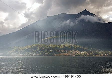 Close-up of Lake Como in a cloudy day with sunshine in Bellagio, a charming tourist village between the lake and the mountains of the Alps. Located in the Lombardy region, northern Italy