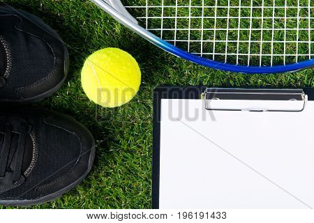 Set for playing tennis lies on a green lawn as a background