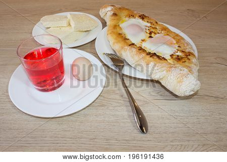 Adjarian khachapuri on a on a plate. Open pie with cheese in the shape of the boat. Delicious homemade khachapuri in Adjarian