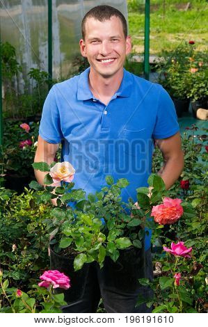The seller of garden flowers shows roses for choice