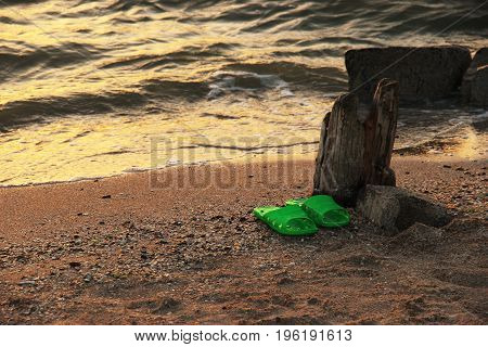 Summer vacation concept. green Flipflops on a sandy ocean beach. The sunset, the beach, the remains of the old pier. Resorts of the Krasnodar Territory Sea of Azov