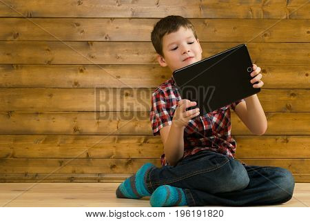 The boy plays enthusiastically in an online game on a wooden background