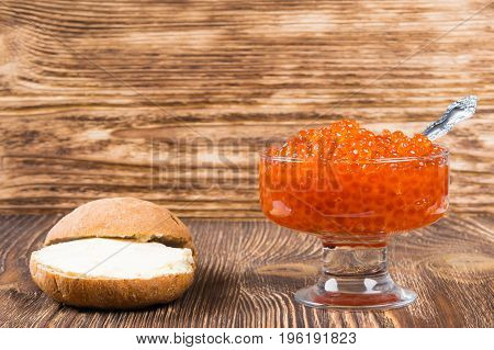 Old wooden background with a plate of red caviar place for inscription