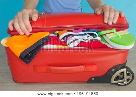 Young woman hands packing suitcase. Travel and vacations concept. Women's clothes and accessories in red suitcase things prepared for travel