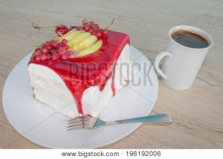 Sliced tasty cake and coffee on wooden table background. Cake with fresh red currant on the plate
