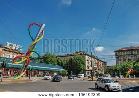 Milan, Italy - May 07, 2013. Street view with cars, colorful modern sculpture and blue sunny sky, at the city center of Milan, a large and modern city. Located in the Lombardy region, northern Italy