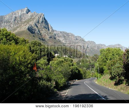 FROM CAPE TOWN, SOUTH AFRICA, WITH A  ROAD IN THE FORE GROUND  LEADING TOWARDS TABLE MOUNTAIN IN THE BACK GROUND AND BUSHES AND TREES ON EITHER SIDE OF THE ROAD