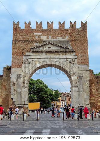 Rimini Italy - June 14 2017: Unidentified people walk under Augustus Arch - the ancient romanesque gate and the historical landmark of Rimini Italy.