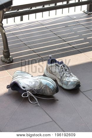 A pair of old and used running shoes laying on a tiled concrete street floor next to a bench