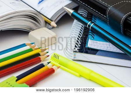 Back to school concept supplies multicolored pencils notepads highlighter pen textbook rubber white desktop learning studying education composition