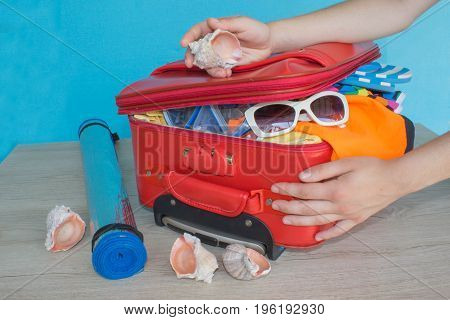 Open red suitcase with clothing on table. Woman packing her red suitcase