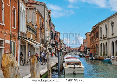 Murano, Italy - May 08, 2013. View of buildings, in front of canal, with people and boats in Murano, a nice little town on top of islands near Venice. Located in the Veneto region, northern Italy