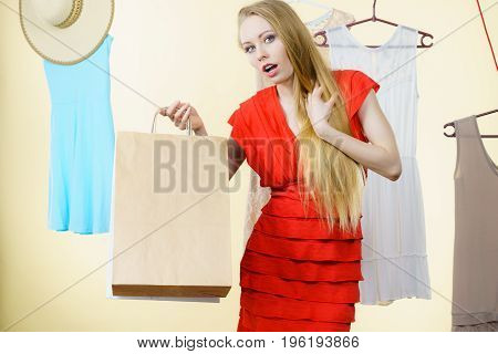 Woman In Shop Picking Summer Outfit