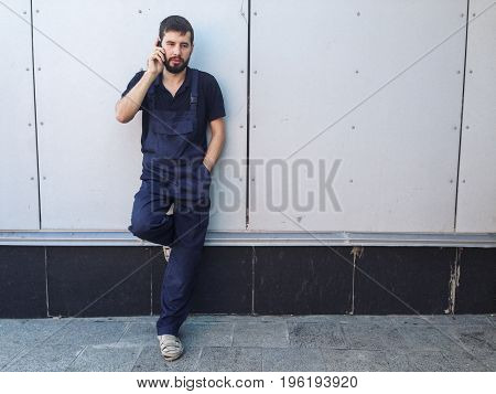 Worker on a break talking on mobile phone standing near the wall